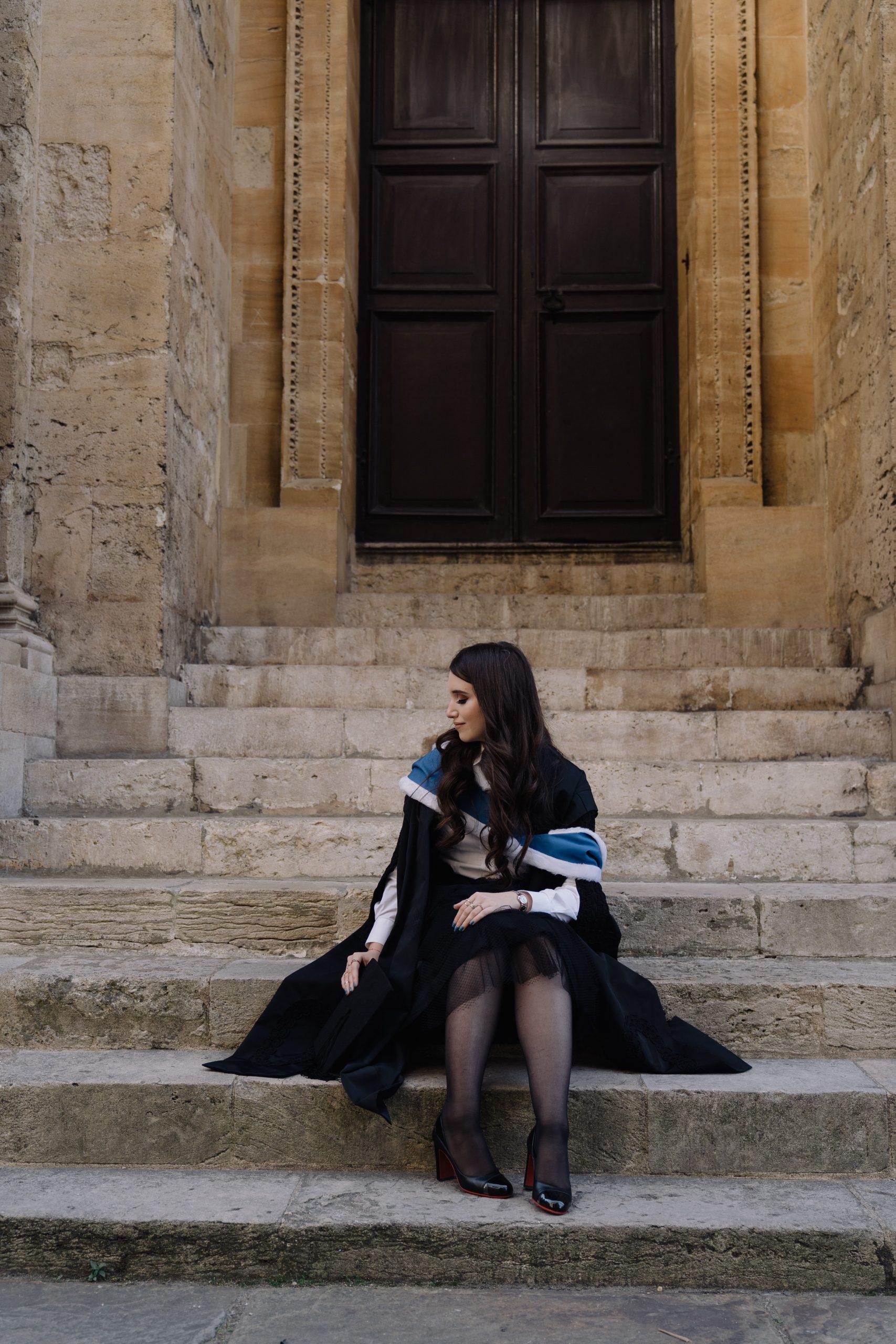 Anna seated at graduation